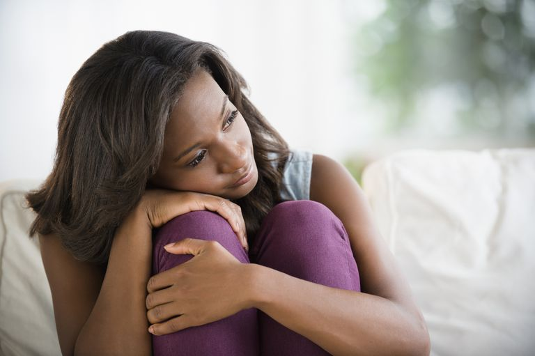 Woman sitting on couch hugging her knees, thinking