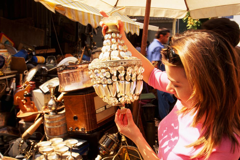 woman shopping for antique chandelier at flea market