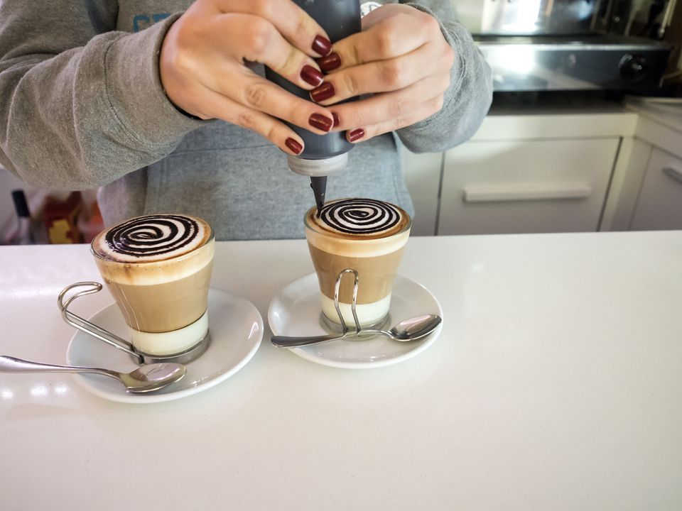 Waitress preparing a coffee with milk condesada and adornments of chocolate on the foam, on the bar of a bar