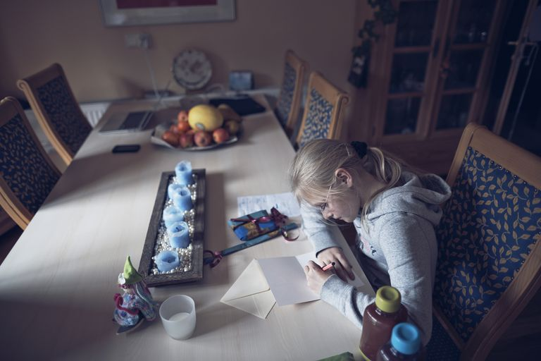 Blond girl writing letter to friend