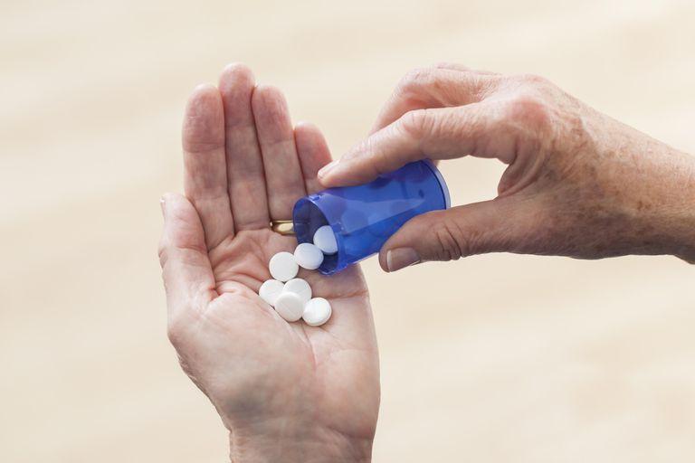 Senior's hand holding prescription pills