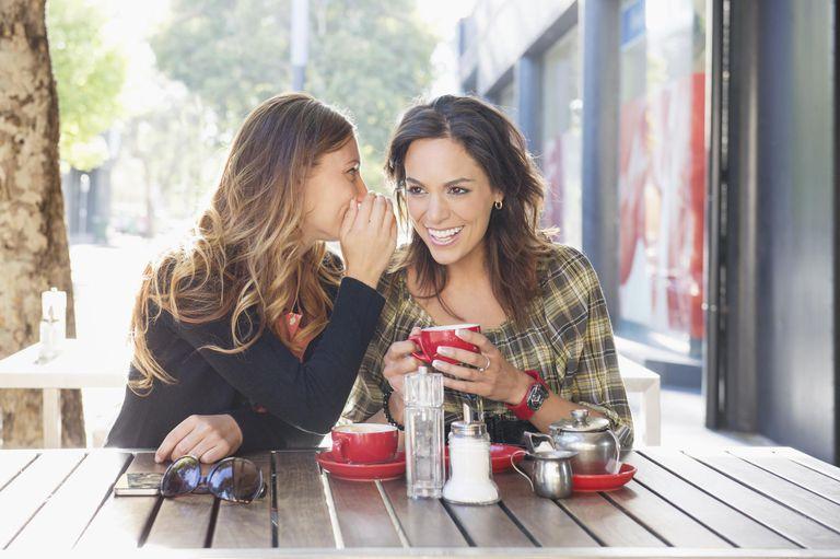 Mixed race women having tea at sidewalk cafe