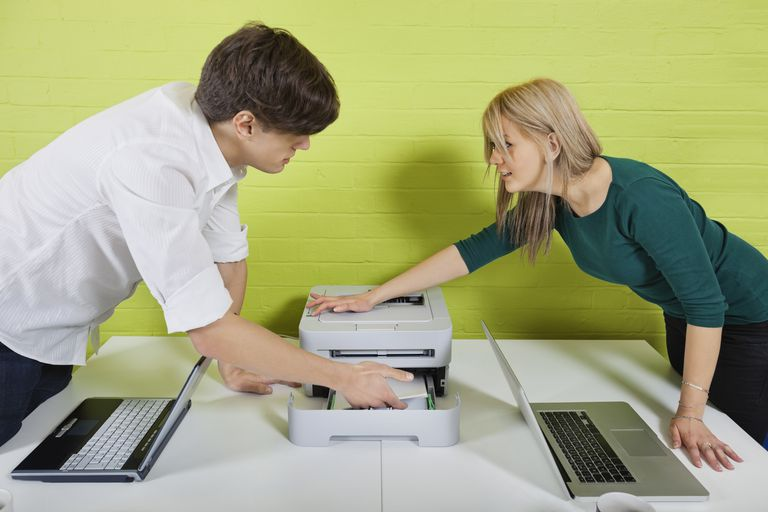 Side view of young businesspeople setting up printer with laptops at desk