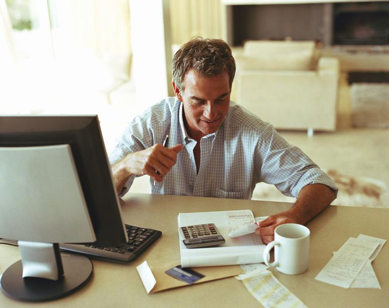 Mature man sitting at desk checking receipts