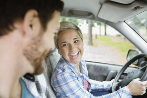 Cheerful young woman looking at man while driving car