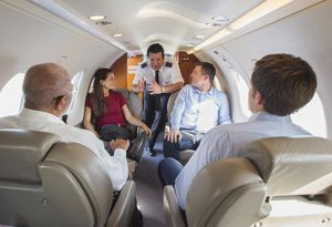 Pilot talking to business people on airplane