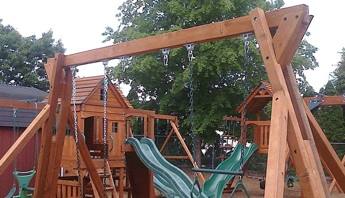 A Wooden Swing Set With Playhouse And Slide