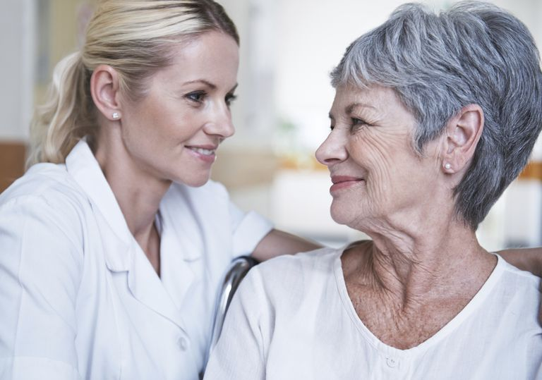 Elderly women smiling at healthcare worker.