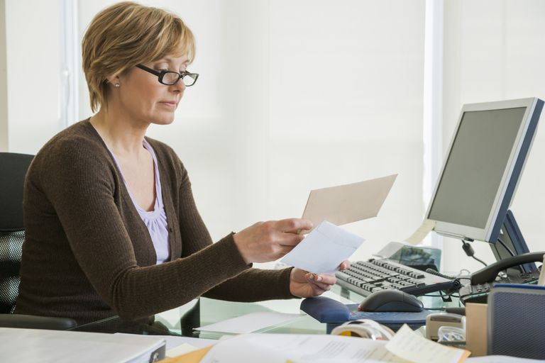 Middle-aged woman looking at paperwork at computer