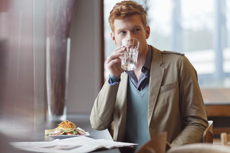 Man drinking water at restaurant