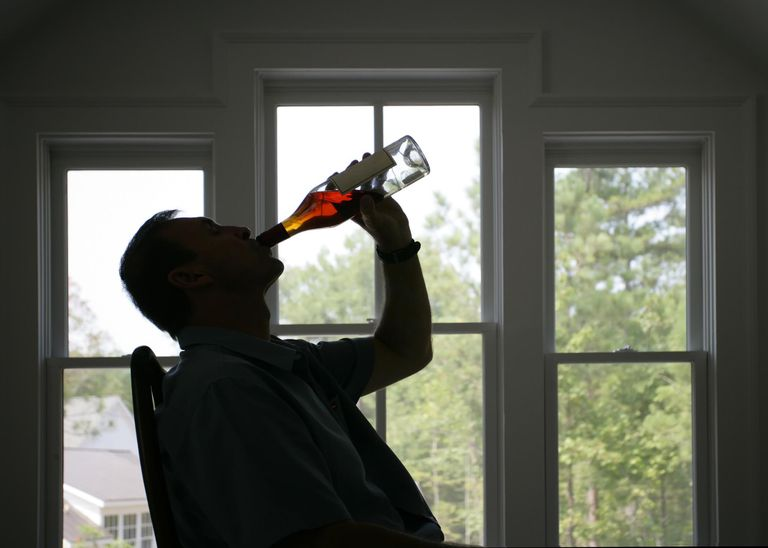 man drinking liquor straight from the bottle
