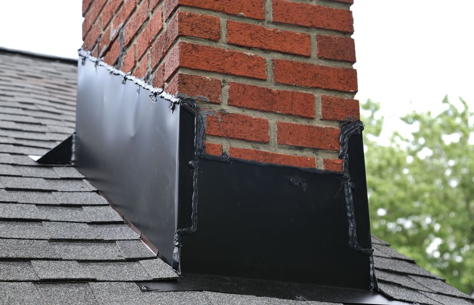 Close-Up Of Brick Chimney On House Roof With Metal flashing