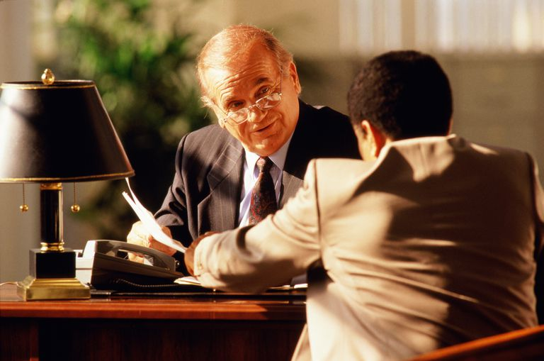 Mature executive sitting at desk, talking to young man