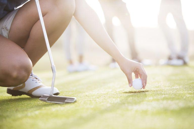 golfer retrieving ball from hole