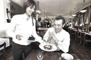 A waitress serves dessert to a customer.