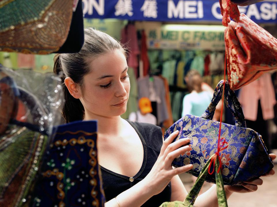 China, Hong Kong, Gage Street Market, woman looking at bag