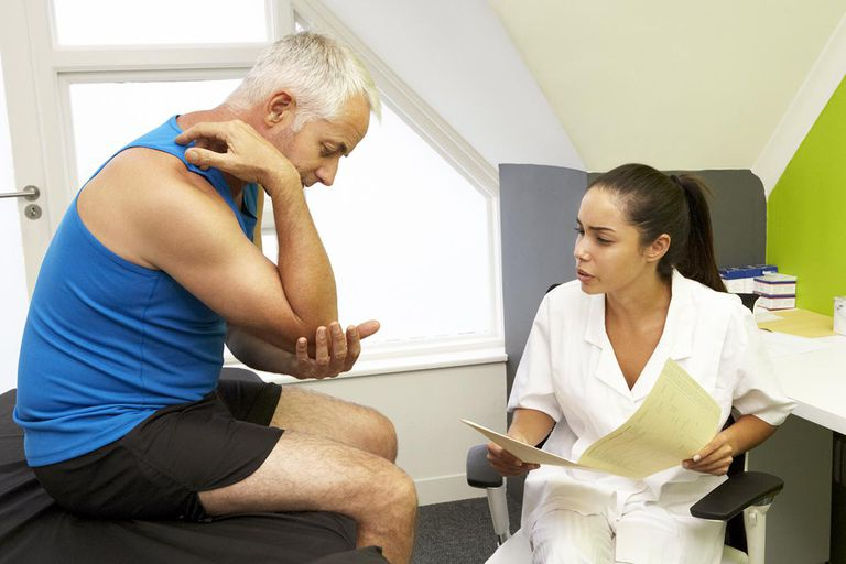 Sports Physiotherapist Treating Male Client Looking At Elbow