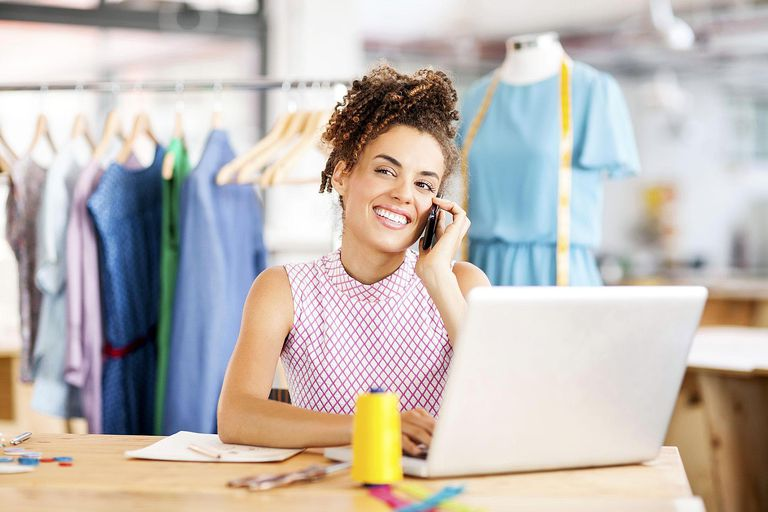Fashion Designer Answering Smart Phone While Using Laptop