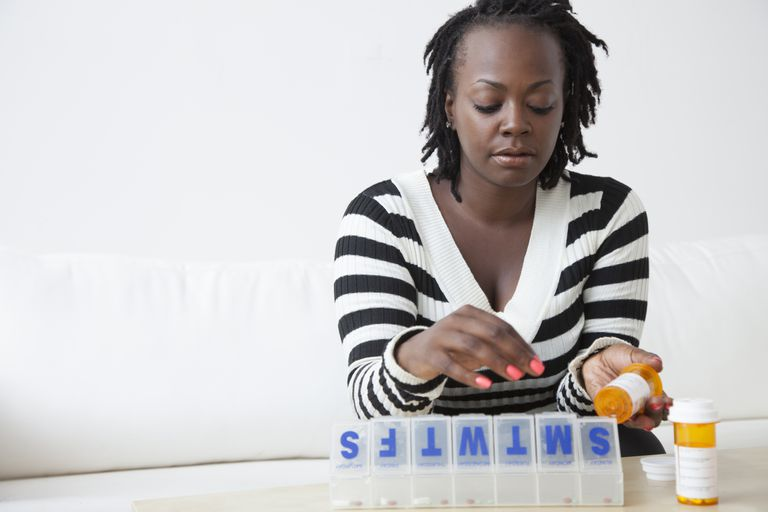 Woman putting asthma medication in her pill box