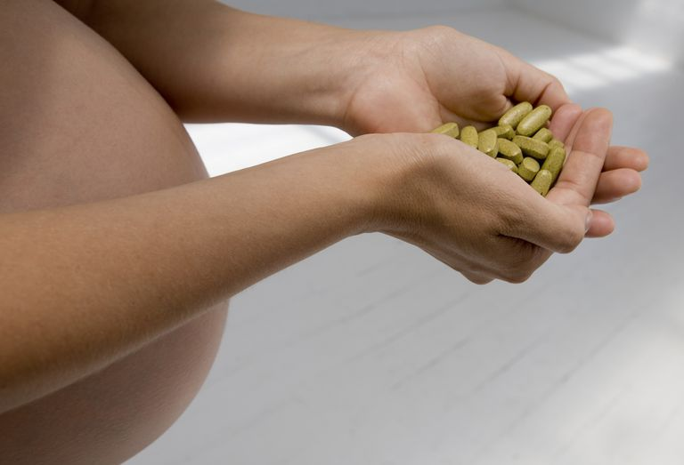Pregnant woman holding pills