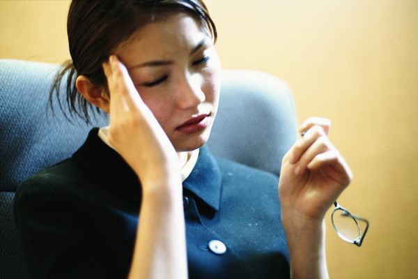 Businesswoman holding finger to forehead