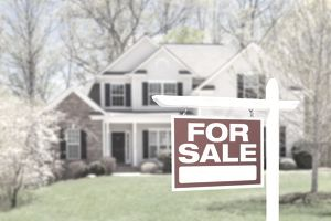a home with a for sale sign in front of it