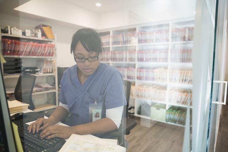 Nurse typing medical record notes at computer
