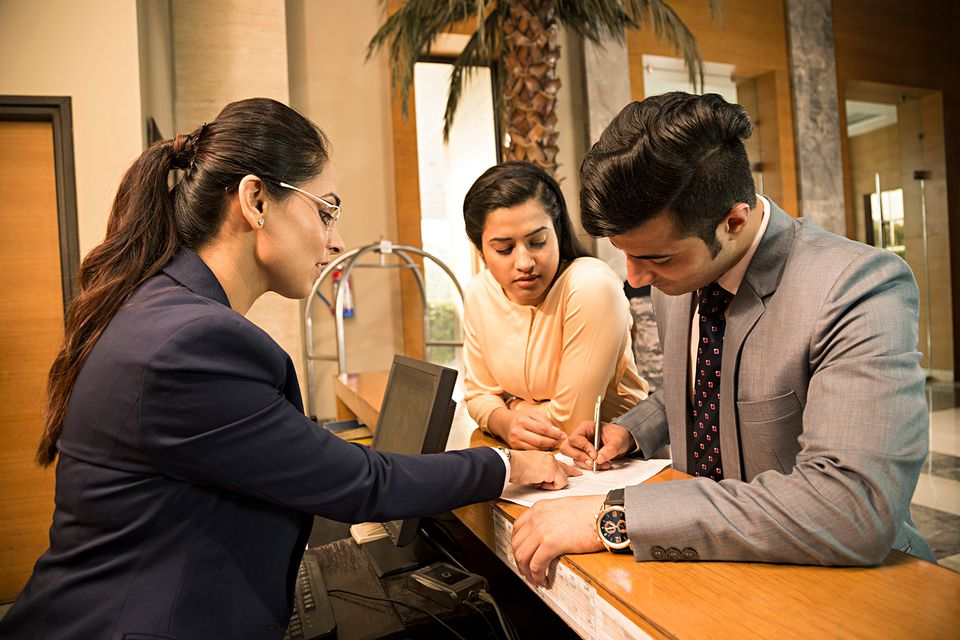 Businessman registering at hotel counter, customer service representative helping businessman.