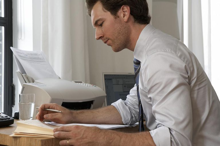 Young businessman sitting at desk reading paperwork
