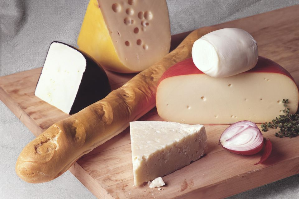 View of a mixed selection of cheeses - Swiss, gouda, Queso blanco, Bel Paese, and Crescenza, and mozzarella - arranged on a wooden cutting board with French bread and an onion, 2004.