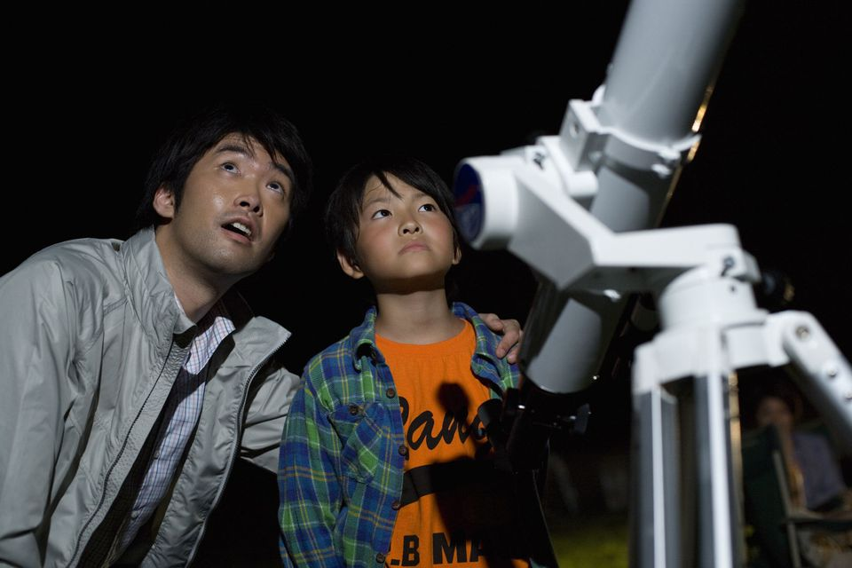 A picture of a father and son enjoying stargazing at night