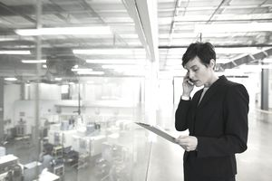 Manager with clipboard talking on cell phone factory