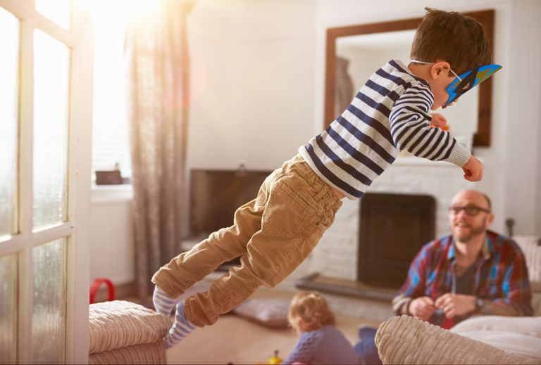 A young boy jumping from one sofa to another A young boy in wrestling mask jumping on one sofa to the other