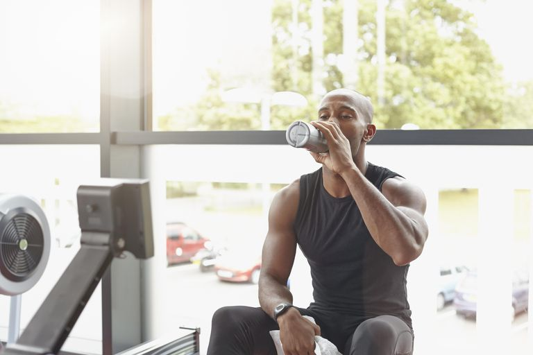 Man in a gym on a rowing machine drinking water