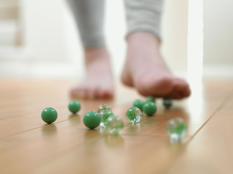 Child about to slip on marbles on the floor