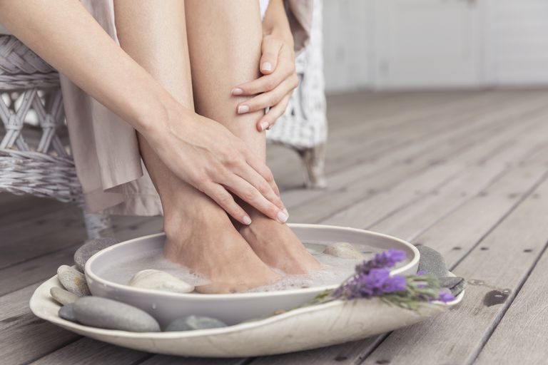 Cropped view of womans feet in foot bath on wooden decking