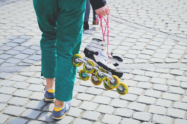 Low Section Of Woman Holding Skates While Standing On Footpath