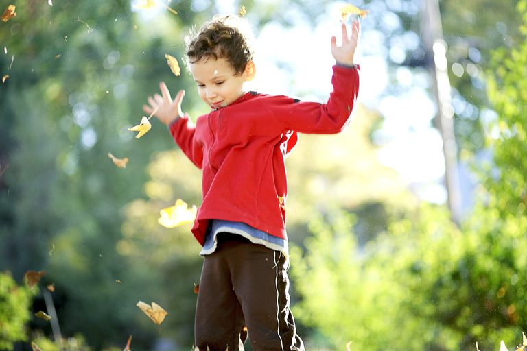 Child tossing autumn leaves into the air