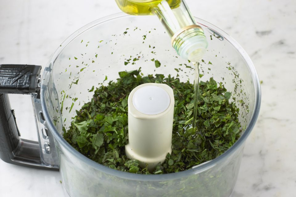 Olive oil poured onto chopped herbs in food processor