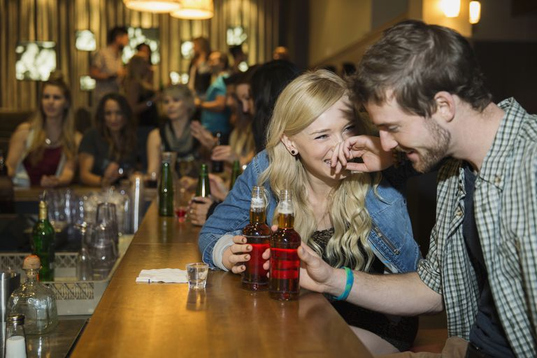 Couple laughing and drinking at bar