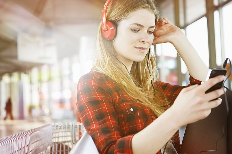 woman with headphones listening to a playlist on iphone
