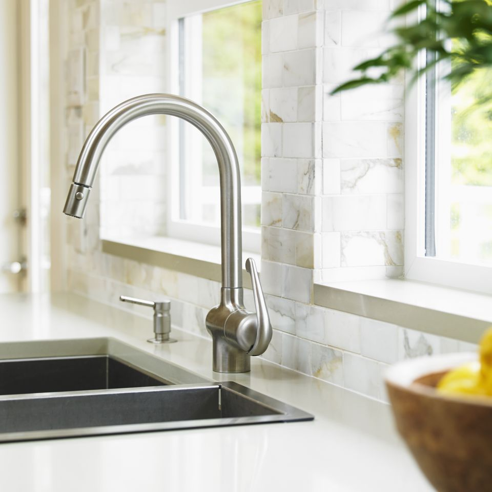 Close-up of stainless steel kitchen faucet with marble subway backsplash