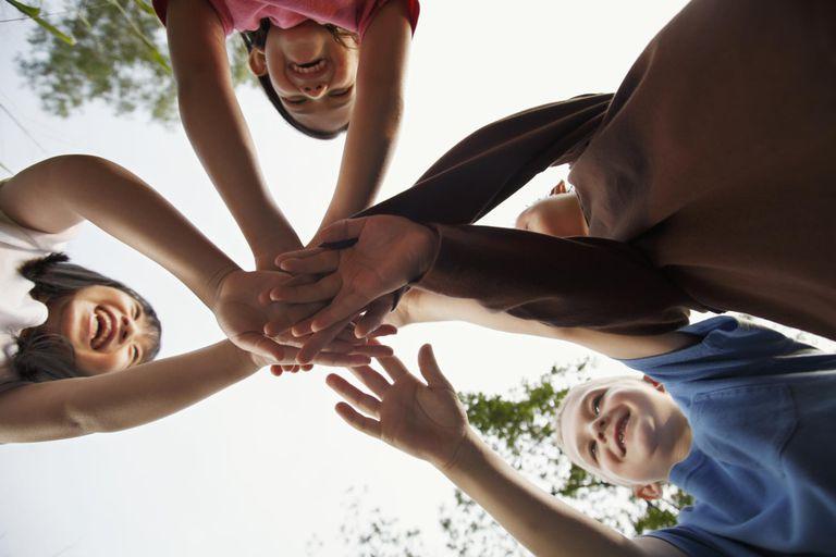 Four children grasping hands.