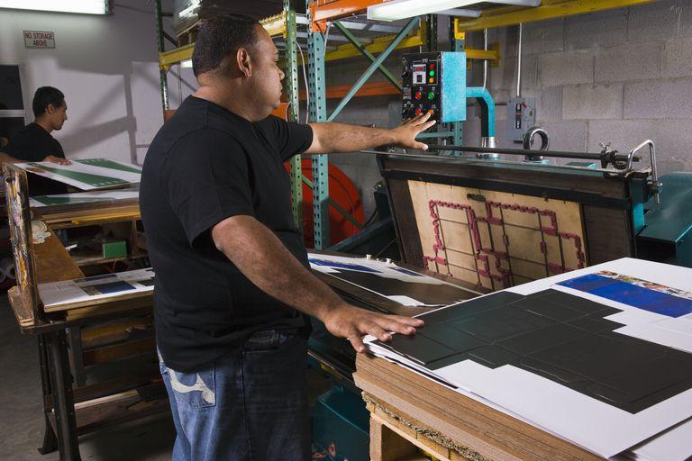 Men using a die cutting machine at print shop
