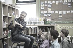 Male teacher reading to children