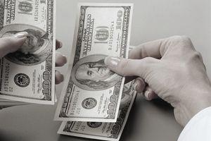 Woman counting 100 dollar bills.
