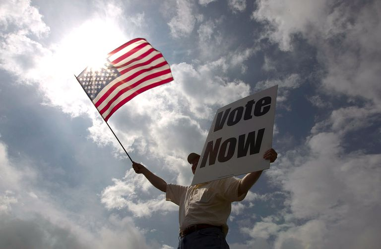 """Man holding US flag and """"vote now"""" poster"""