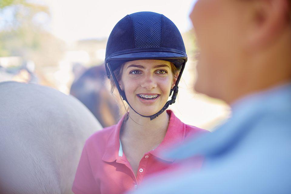Girl wearing black riding helmet.