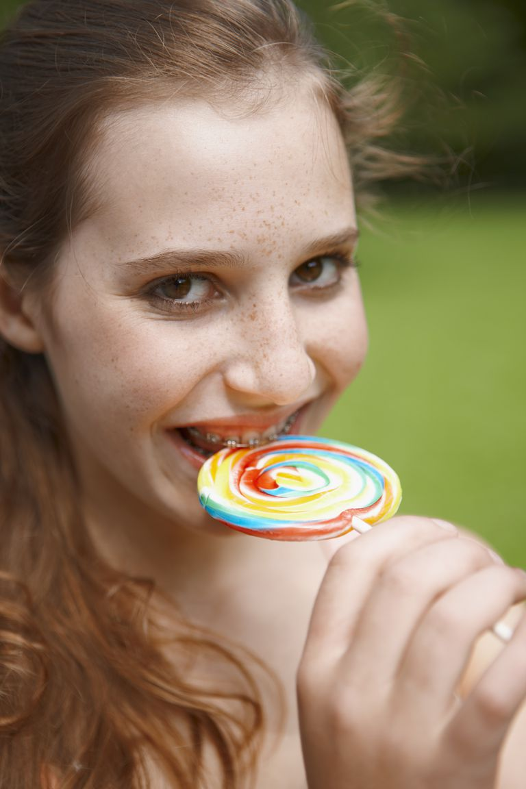 Young girl eating a lollipop in a park
