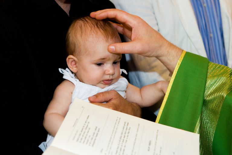 Priest is baptizing little baby in church